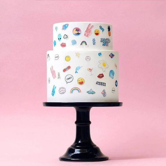 "wedding ideas for cakes—two-tiered white cake with small emoji ""stickers"" adorning on a black pedestal stand"