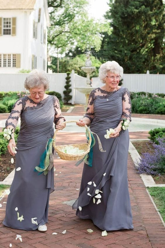 wedding ideas for ceremony attendants—flower grandmas walking down the aisle in matching grey dresses sprinkling white petals as they walk