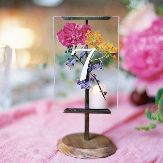 wedding ideas for table numbers—pressed flowers in a glass frame with a wood pedestal stand with the table number on the front