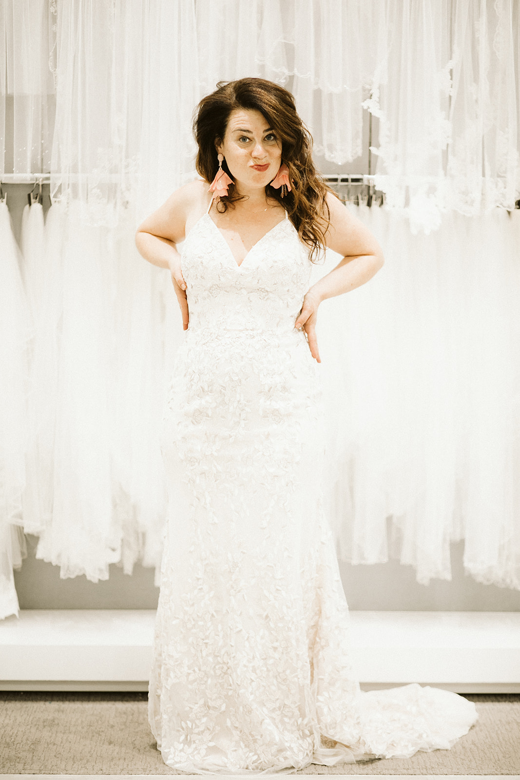 A woman with long brown hair stands with her hands on her hips and purses her lips while wearing a spaghetti-strap lace gown at David's Bridal
