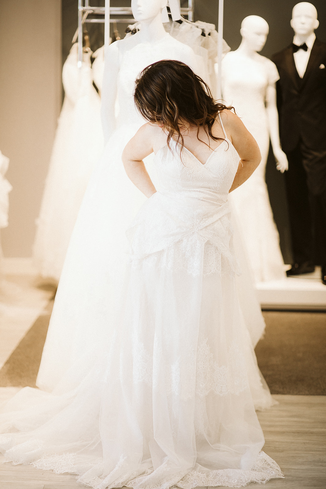 A woman with long brown hair begins to remove the outer dress (a sleeveless v-neck) to reveal a spaghetti-strap gown underneath at David's Bridal