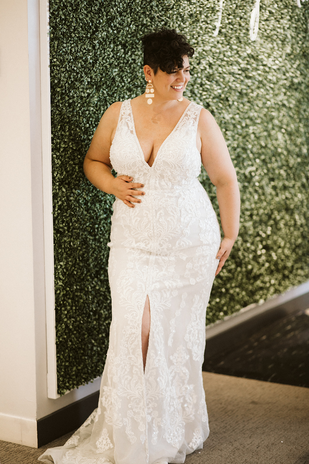 A curvy brunette woman wears a form-fitting sleeveless wedding gown with a plunge v-neckline and high center slit as she stands in front of a greenery wall at David's Bridal