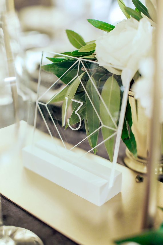 Winter wedding ideas for table numbers—Acrylic table number on table with greens in back