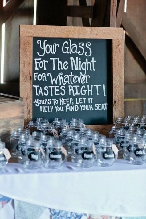 "wedding ideas for cups—customizable mason jars. A sign reads ""Your Glass for the night for whatever tastes right! Yours to keep, let it help you find your seat"" above rows of mason jars with handles with names written on the side"