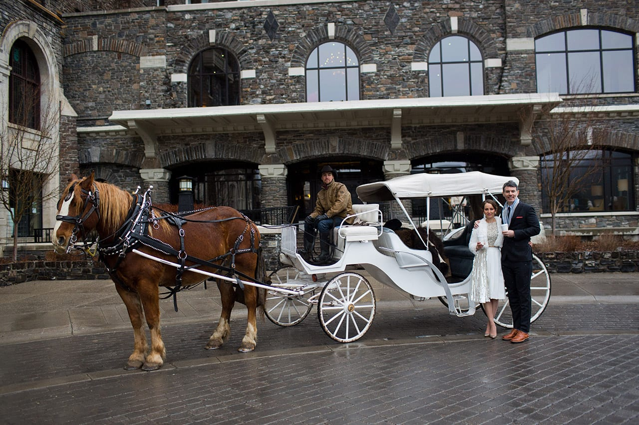 Winter wedding ideas for transportation—Woman in white dress and man standing in front of horse drawn carriage