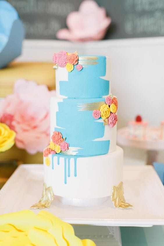 "wedding ideas for cakes—a hand-painted cake with blue and silver streaks on three tier cake with gold leaf ""feet"" and pink, yellow, and orange edible rosettes"