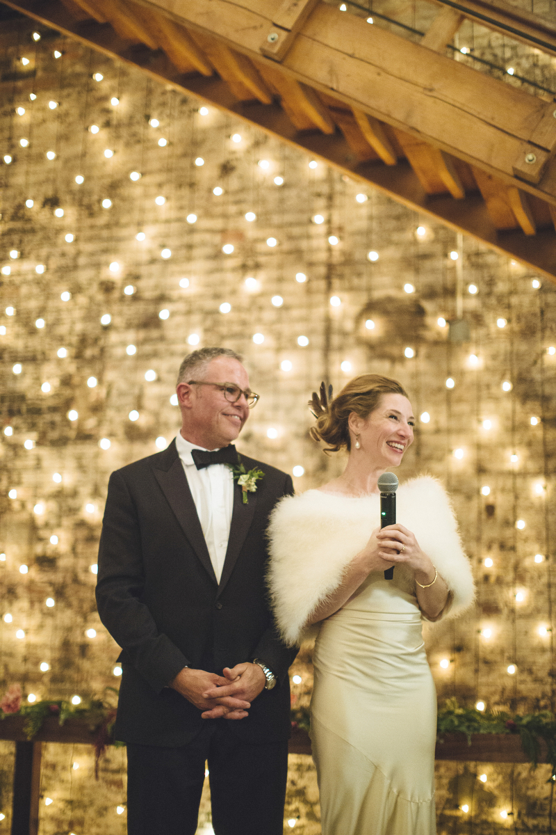 Winter wedding ideas for backdrops—a couple standing in front of a wall of string lights