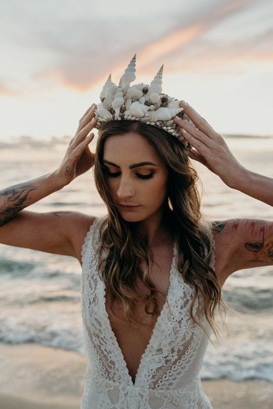wedding ideas for headpiece—woman wearing a shell crown in a wedding dress with waves crashing behind her as the sun sets