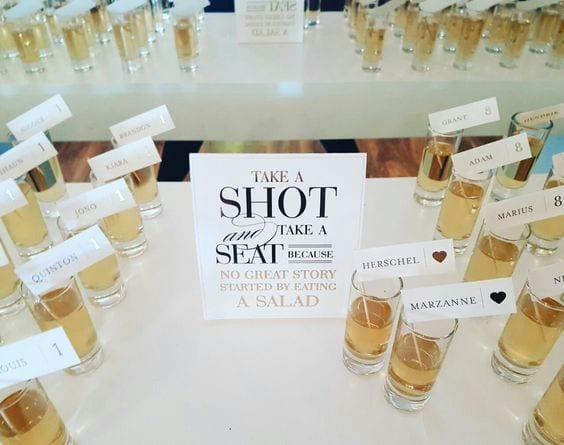 "Wedding ideas for a seating chart—shots seating charts with a sign that reads ""Take a shot and take a seat because no great story started by eating a salad"" with rows of shot glasses with flags with names and table numbers"