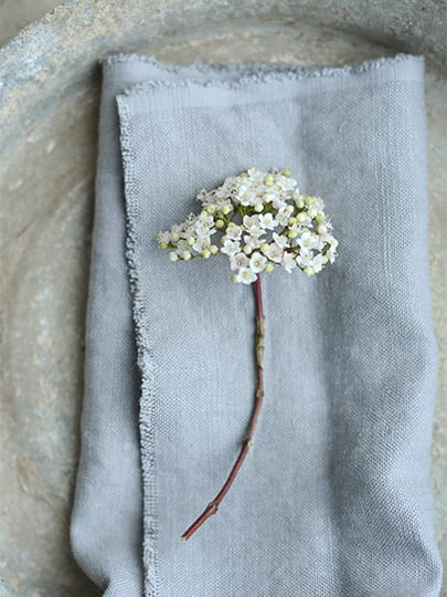 Winter wedding ideas for place settings—Grey napkin with white flowers on top