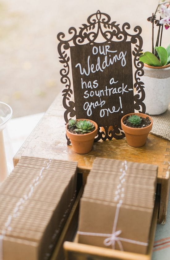 "Wedding ideas for a wedding soundtrack—chalkboard sign that reads ""Our Wedding has a soundtrack—grab one!"" above rows of cds packaged in kraft"