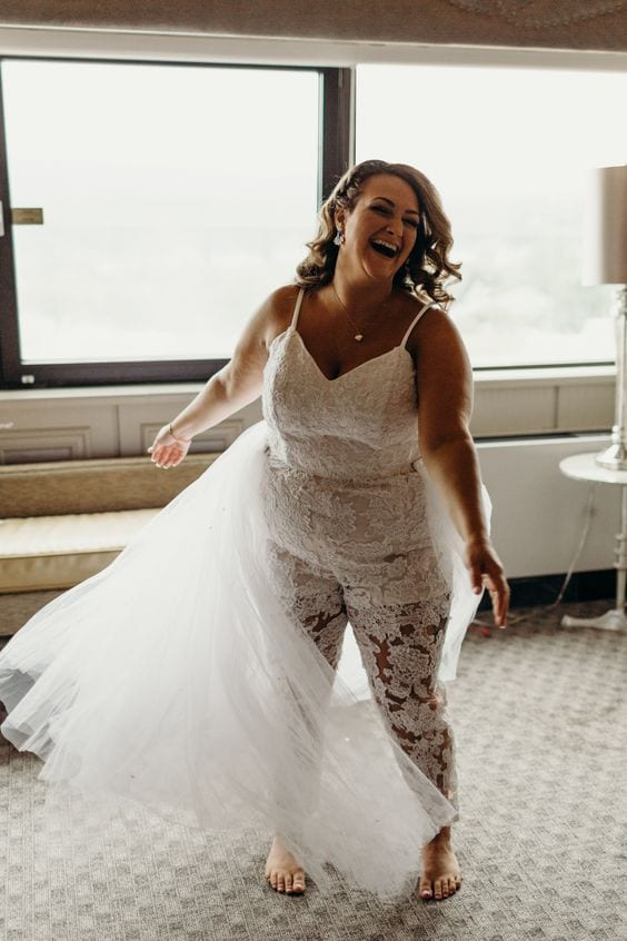 wedding ideas for a bride in a lace jumpsuit, mid twirl, laughing