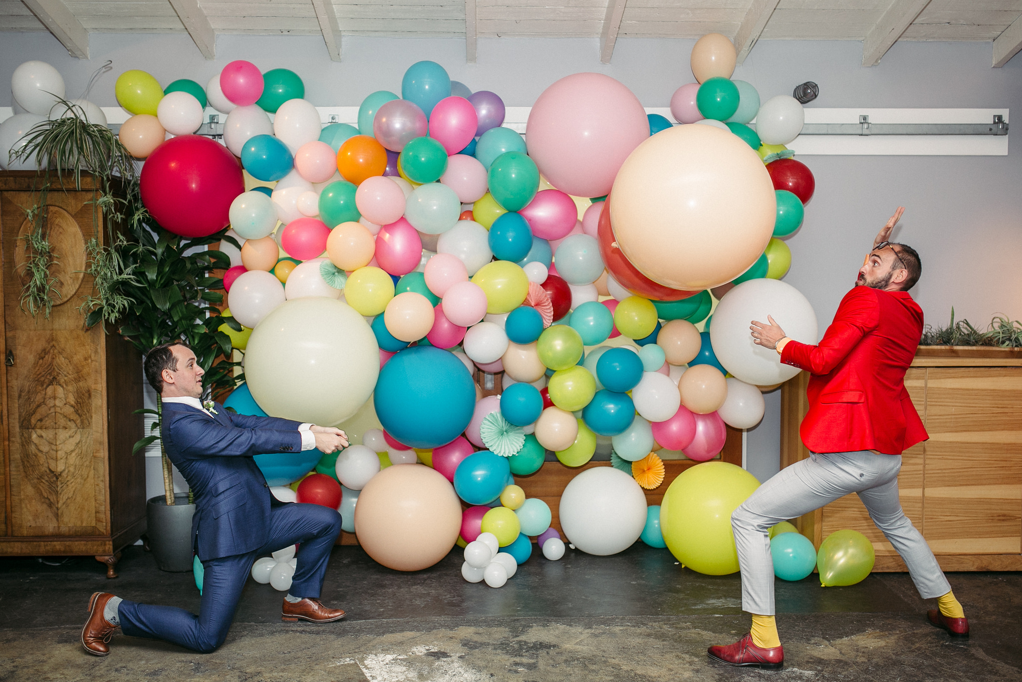 Two men in suits play with giant balloons in front of a colorful balloon installation