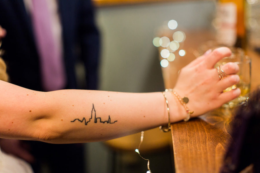 A woman with a line drawing tattoo on her forearm rests her hand on a bar near a whiskey glass. Twinkle lights shine out of focus down the bar.