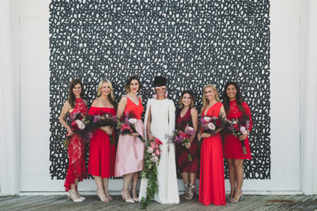 A bride in sunglasses and a cape dress stands among her six bridesmaids in different styles and shades of red dresses in front of a black and white number wall.