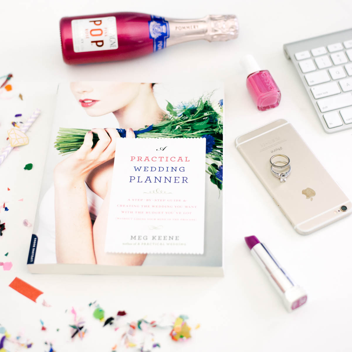 the a practical wedding planning guide on a white desk surrounded by champagne, makeup an iphone and confetti