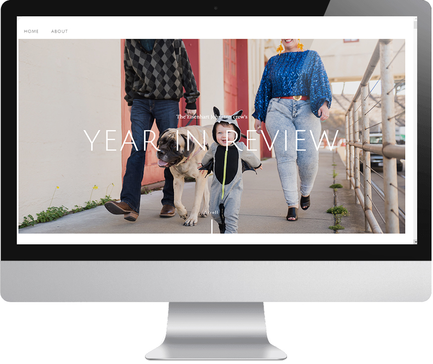 """A computer monitor displaying a page from a Squarespace family website features an image of a man, woman, baby in a grey bat hooded onesie, and English Mastiff on a leash walking toward you in an urban scene. The text, """"The Eisenhart-Johnston crew's Year In Review,"""" reads overlaying the image."""