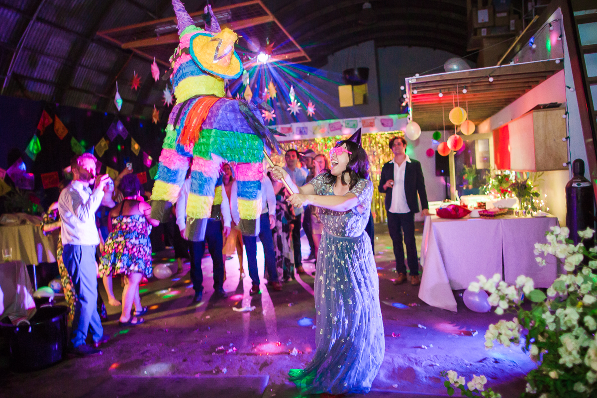 A woman in a formal occasion dress and hot pink sunglasses smiles joyfully as she strikes at a colorful burro piñata at a brightly lit outdoor wedding reception