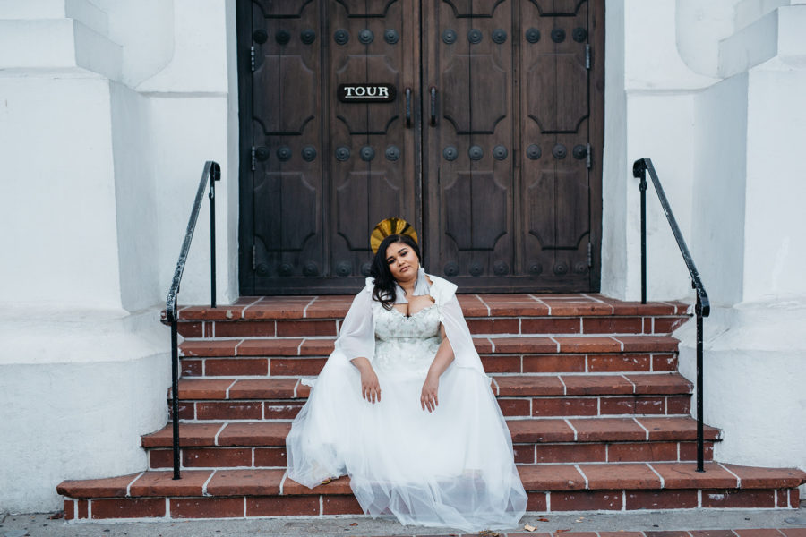 A woman in a radiant crown and a plus size wedding dress with a cape from Lace and Liberty x APW sits on terra cotta steps in front of brown wood doors