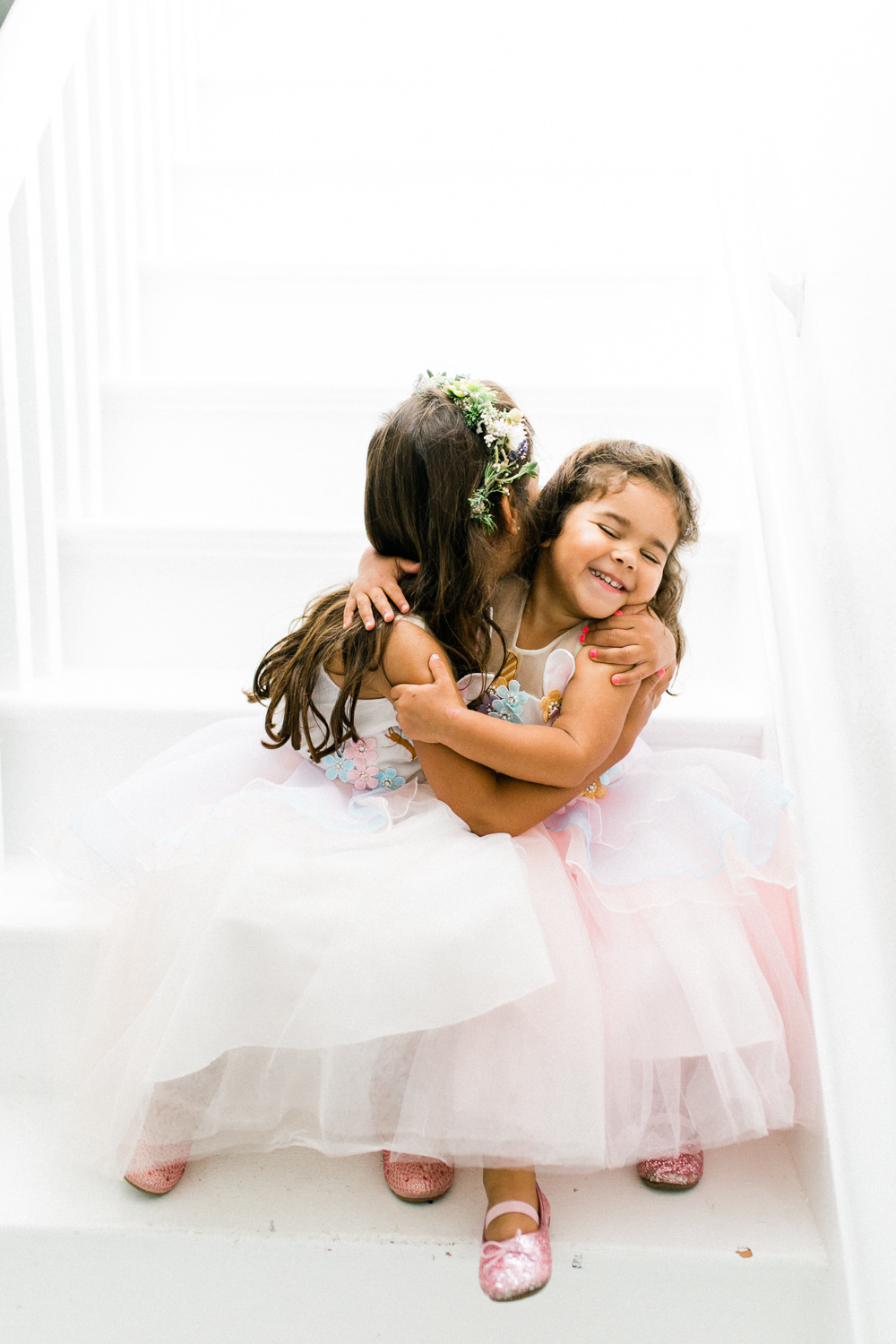 two young flower girls in tulle dresses and sequined slippers sit on a staircase and hug