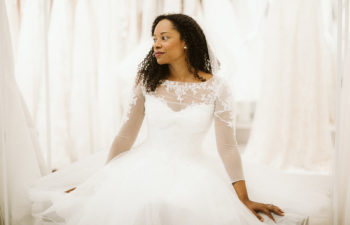 A woman sits in a bridal fitting room wearing a long sleeve wedding gown. She looks to one side, thoughtfully.
