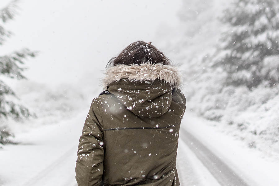 A woman in a fur trimmed parka walks away from you down a snowy lane