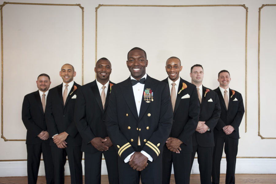 A Marine groom in uniform jacket and bow tie is flanked by six groomsmen in tuxes. All are smiling.