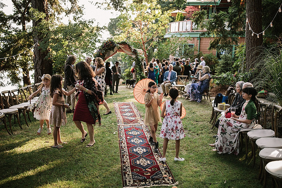 ideas for backyard weddings - A converted backyard space filled with people and a rug aisle perfect for backyard weddings
