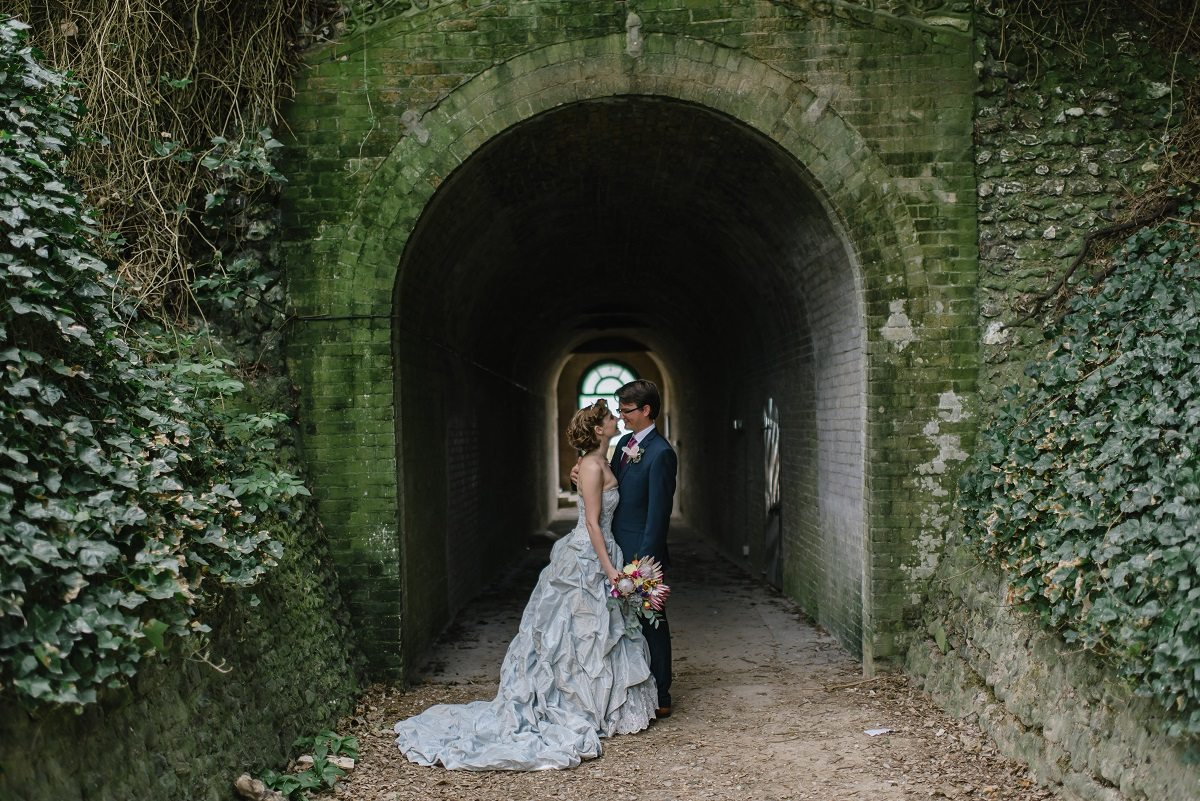 A couple in a wedding dress and tux stand at the moss- and ivy-covered opening of an old brick tunnel, smiling at each other at their destination wedding