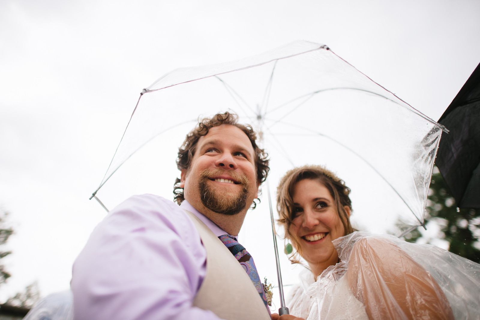 a couple smiling huddling under a wedding umbrella for rain while wearing a clear plastic rain ponchos