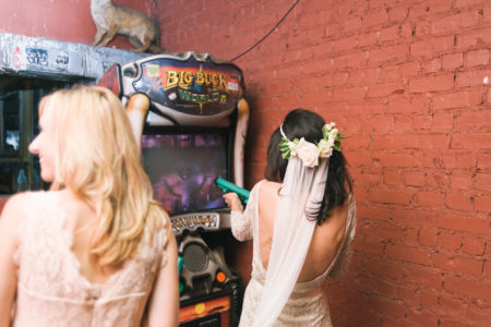 A woman in a wedding dress and veil plays a shooting arcade game, aiming the plastic weapon at the screen