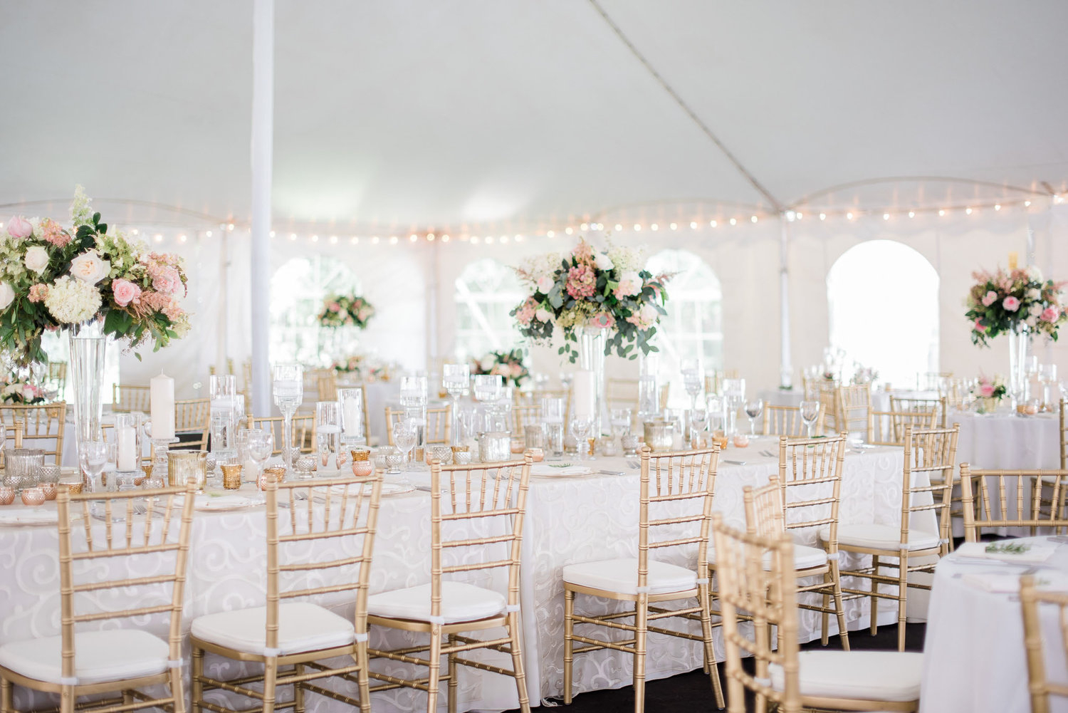 Gold Chiavari chairs at a white and blush tent wedding reception with raised flower arrangements on the tables.