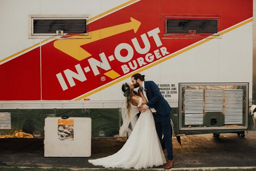 weddings ideas of a couple in a wedding dress and suit kissing in front of in and out truck