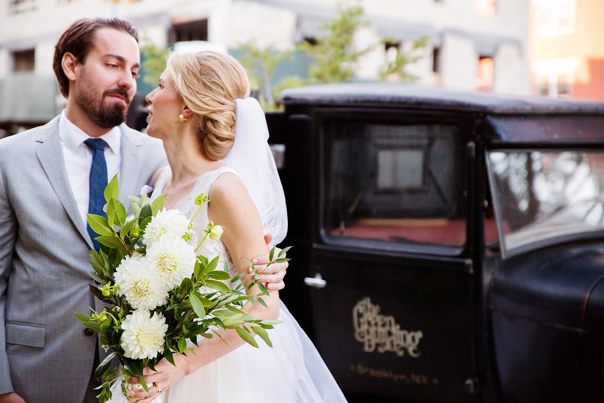 Groom with his arm around bride holding a large bouquet of with white flowers and greenery with The Green Building vintage black truck in the background in a photo by Kyo Morishima