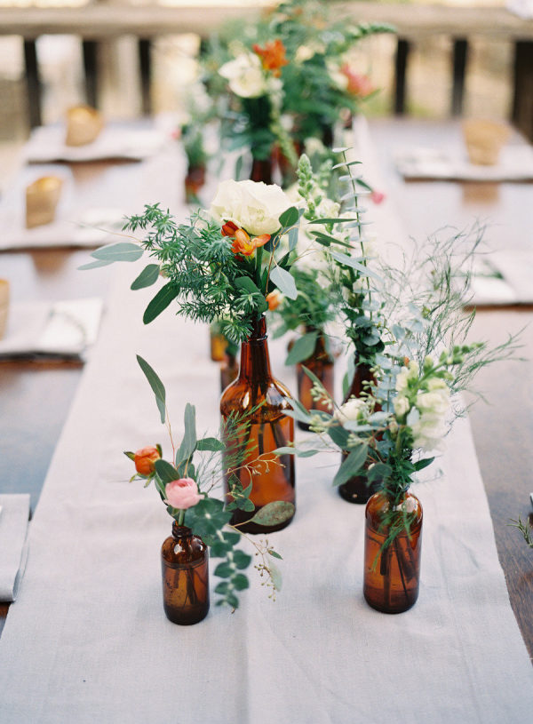 Flowers and leaves in bottles on a long table as an idea for bridal shower decorations