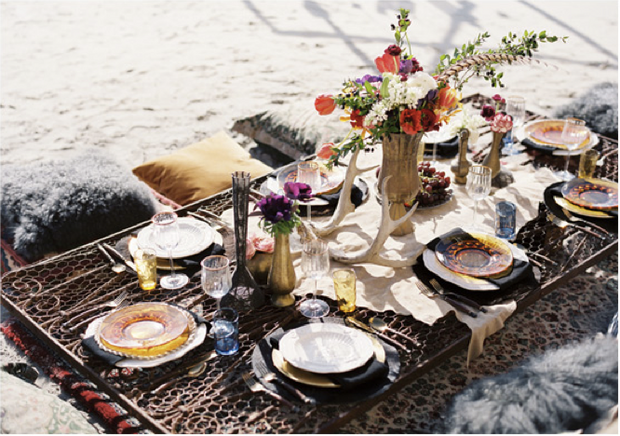 a low table on a beach with pillows and full table setting as an idea for bridal shower decorations