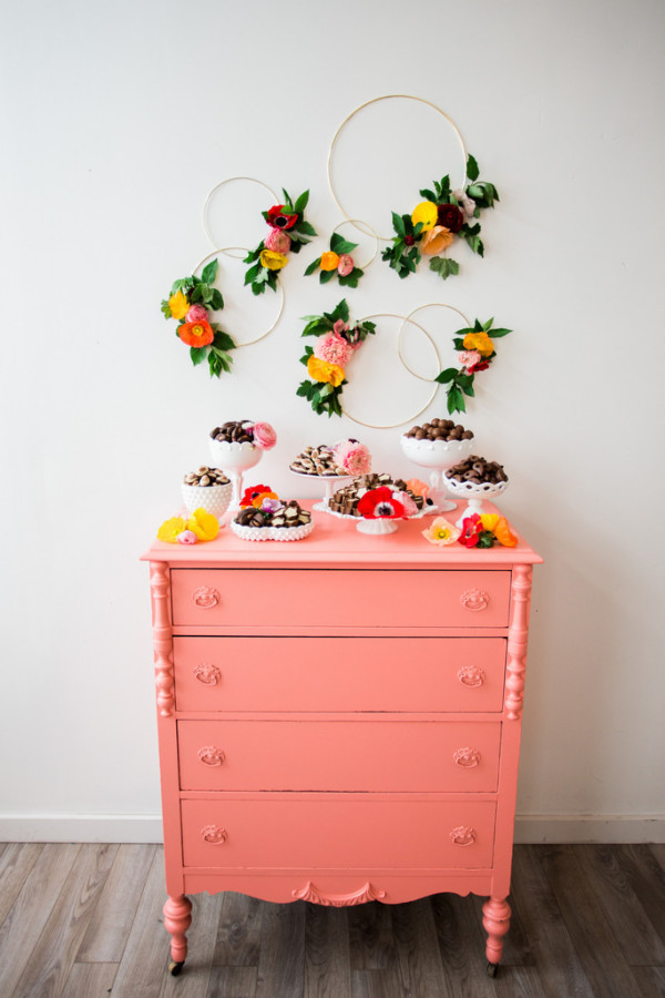 Hoops with flowers over a bureau holding desserts as an idea for bridal shower decorations