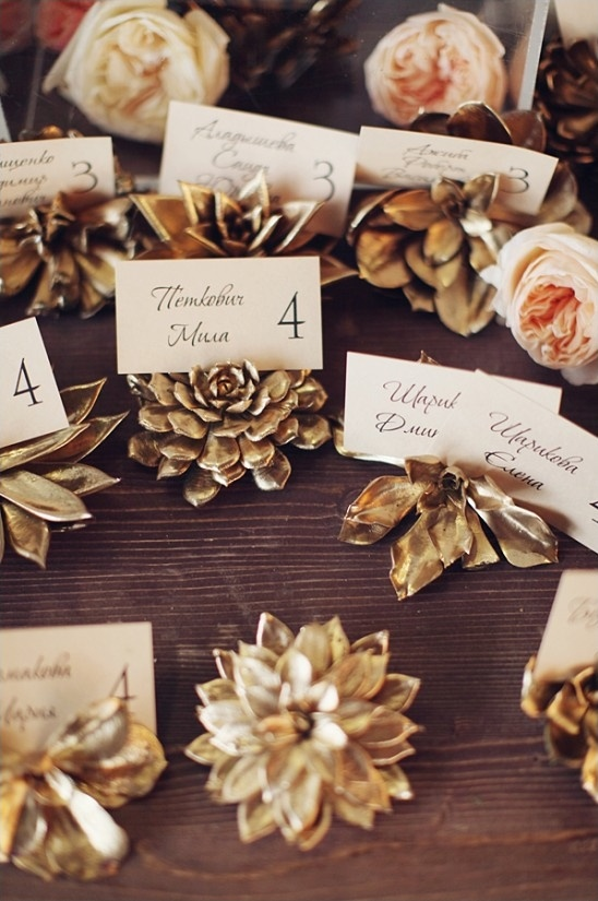 Gold spray painted succulent escort card holders as an idea for bridal shower decorations