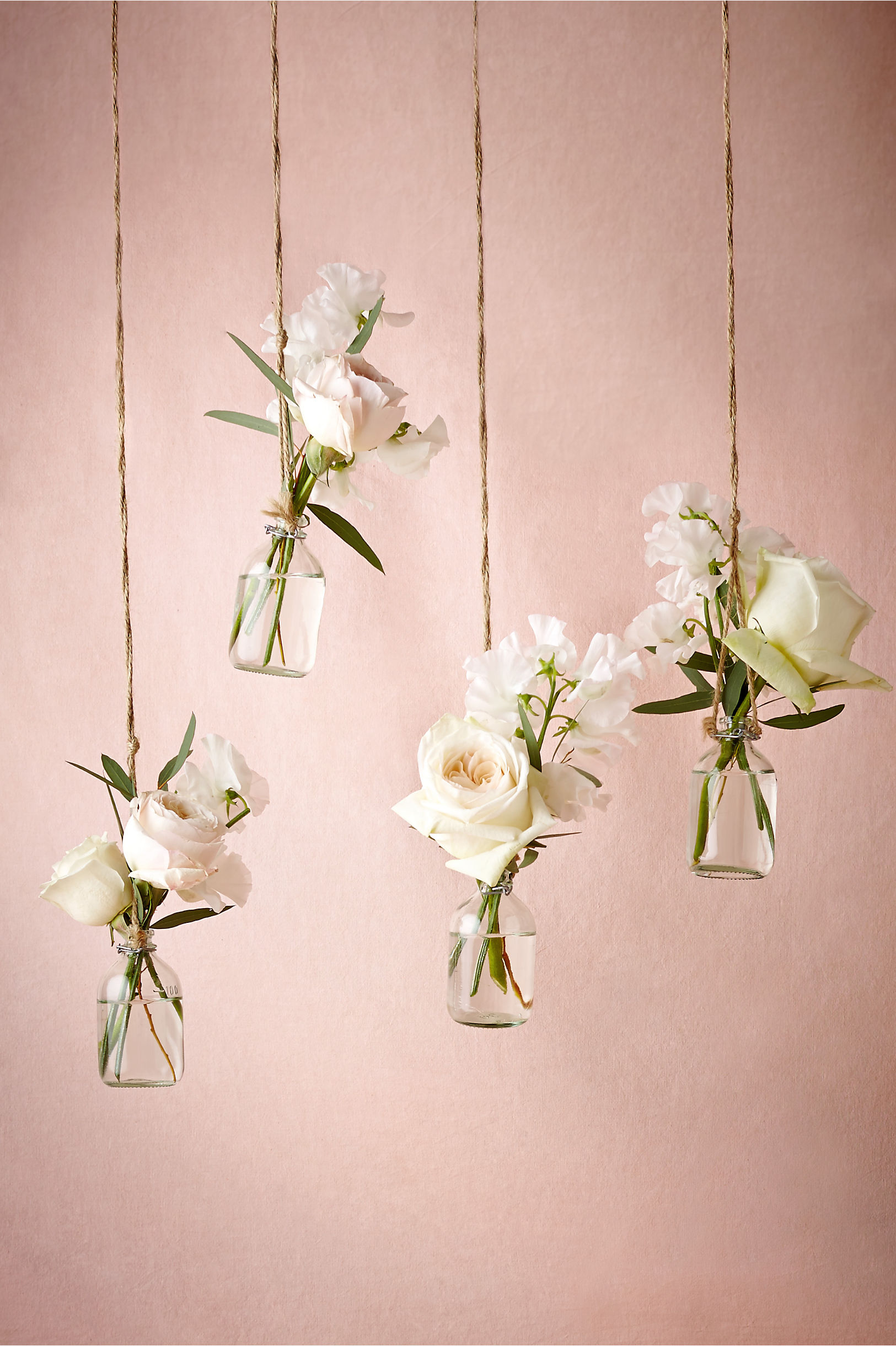 Hanging bud vases in front of a pink wall as an idea for bridal shower decorations