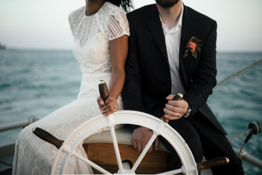 A couple in wedding clothes hold the wheel of a yacht on the water