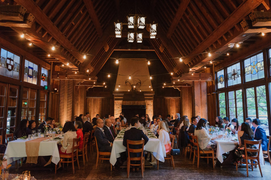 A large party gathers at several family-style tables in a large, high-windowed hall to celebrate an engagement party