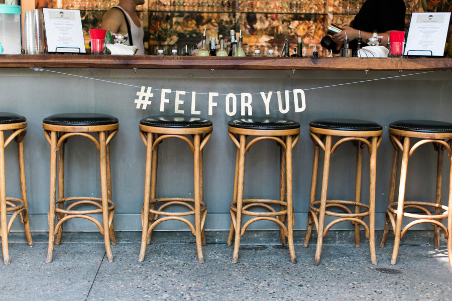 "Barstools in front of a bar with a sign hanging above that reads ""#FELFORYUD"""