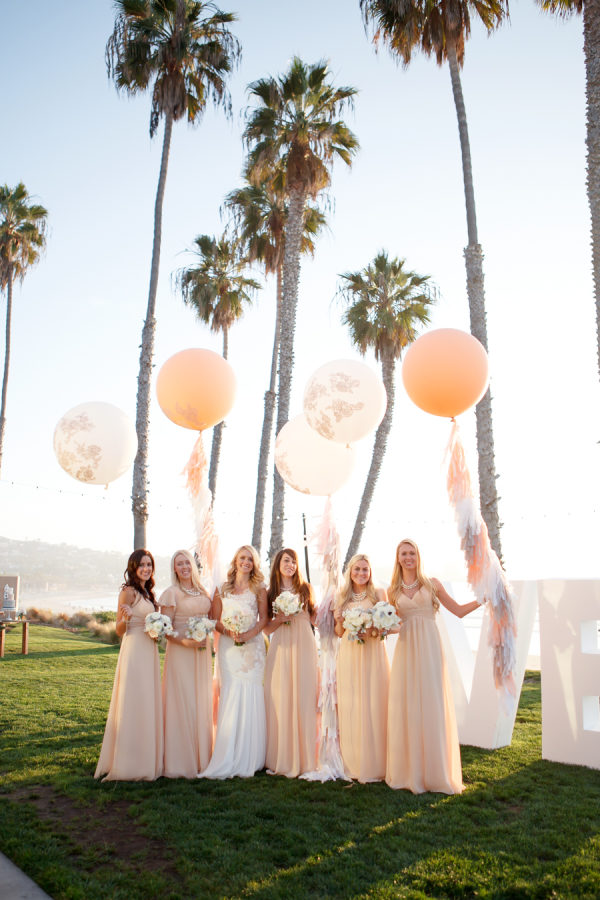 A group of women holding oversized balloons among palm trees as an idea for bridal shower decorations