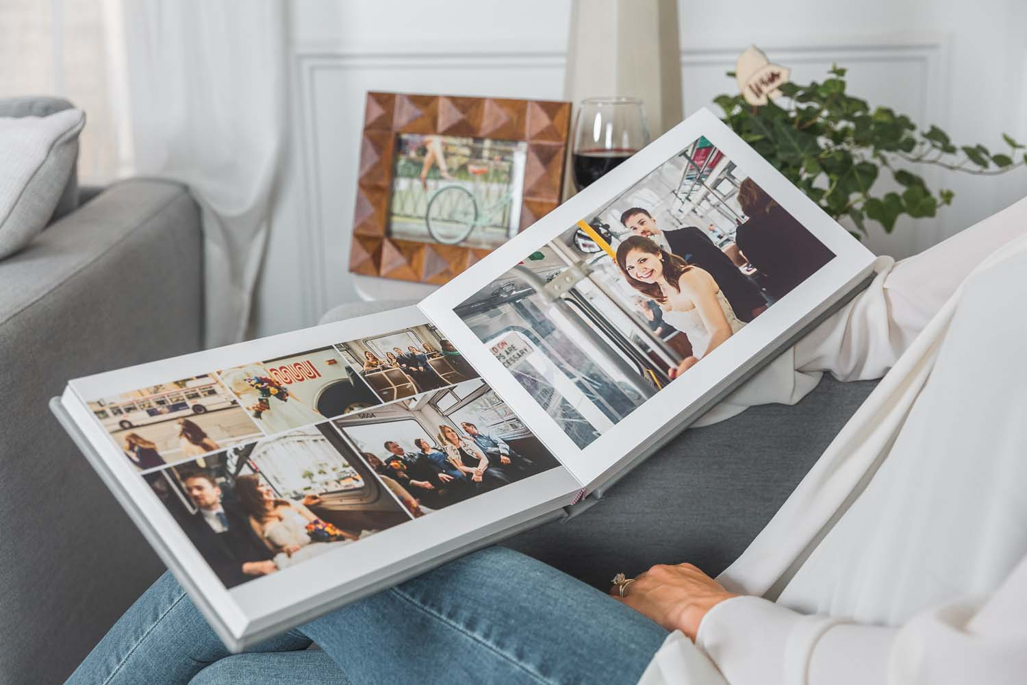 medium close up of a flat lay wedding album open on a woman's lap by Albums Remembered