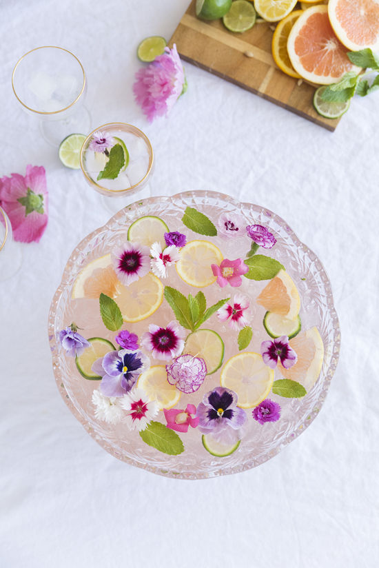 engagement party ideas for punch bowl filled with fruit and flowers on white tablecloth