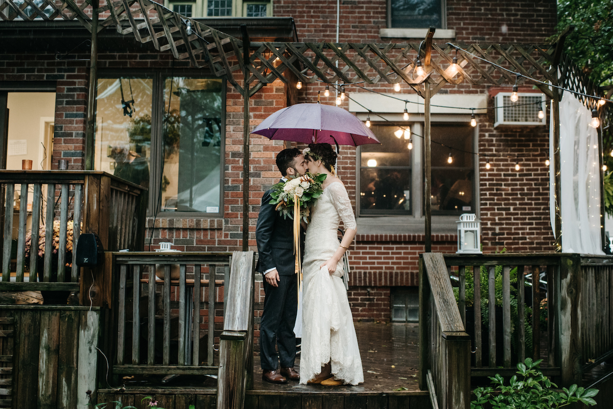 a couple kissing under an umbrella in a restaurant backyard