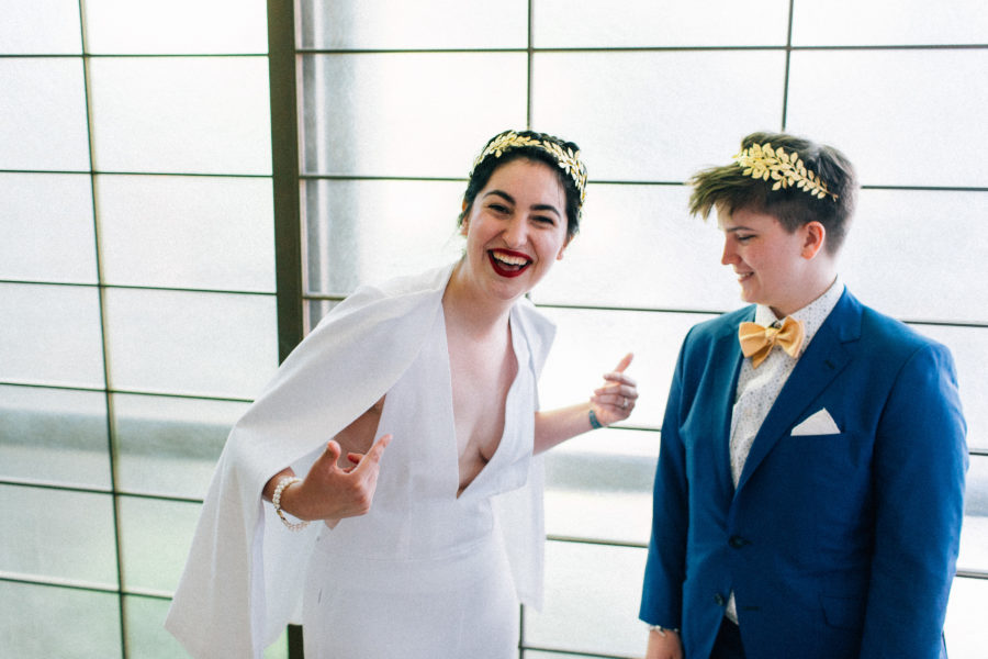 A queer couple in a wedding dress and a suit with bow tie. The person in a wedding dress laughs and points at themself, while the person in a suit smiles and looks on.