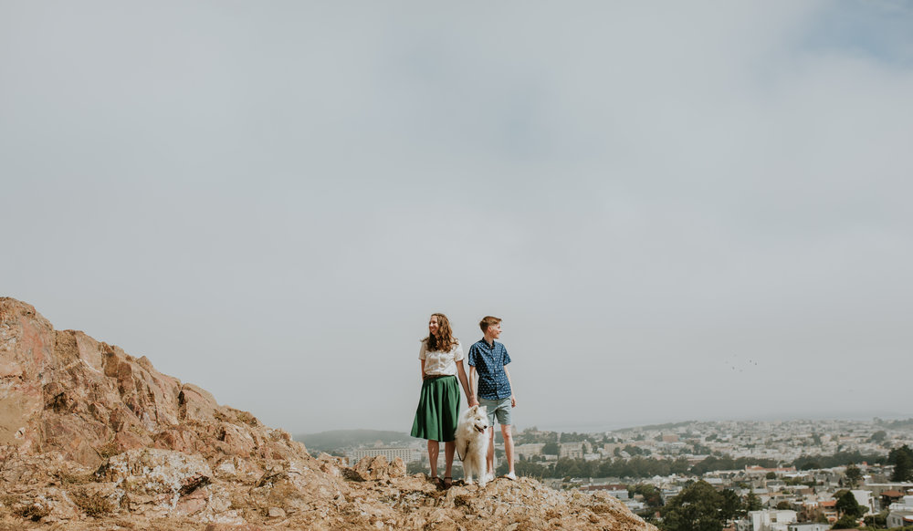 a couple stands on top of a desert hill looking in opposite directions with their dog between them for an engagement session