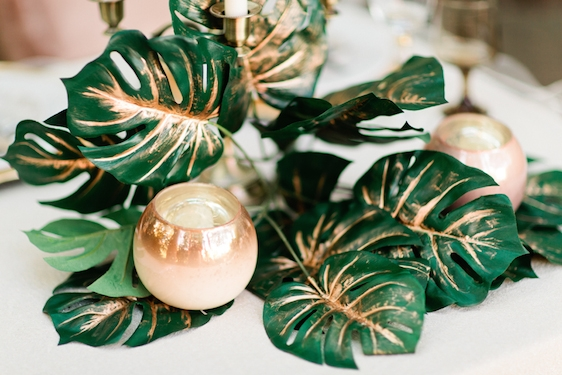 Gold painted leaves with a candle on a table as an idea for bridal shower decorations