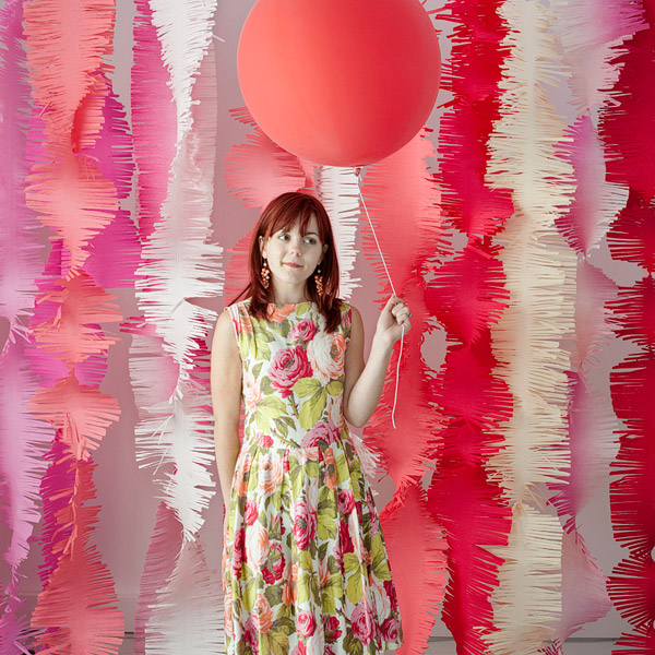 Woman standing in front of streamers with a coordinating balloon as an idea for bridal shower decorations